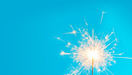 Wick with lit gunpowder from which many yellow sparks come out on blue background