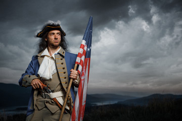 Soldier of United States War of Independence with flag and pistol posing over dramatic sky. 4th july History Concept photo