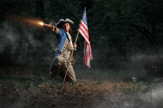 Man dressed as soldier of War of Independence United States aims from pistol with flag