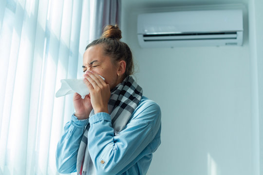 Sneezing woman caught a cold from the air conditioner at home. Conditioner disease