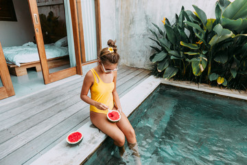 Girl eating watermelon in pool on luxury villa in Bali