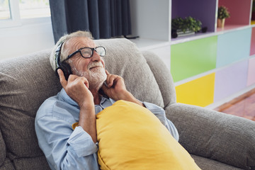 senior man happiness sitting on the sofa and listening music with headphone at living room for relaxing