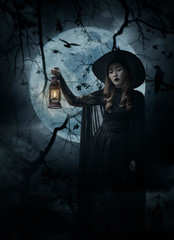 Halloween witch holding ancient lamp standing over cross, church, crow, birds, dead tree, full moon and cloudy sky, Halloween mystery concept