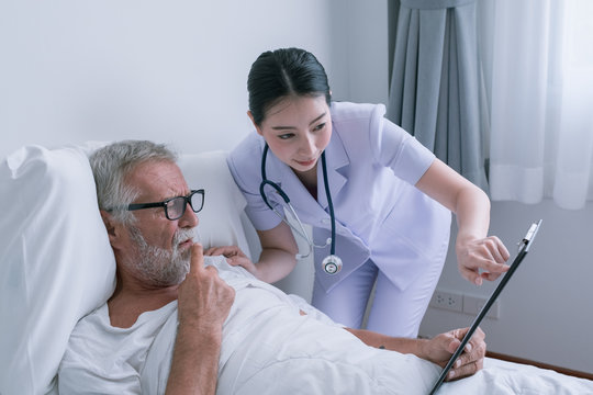 senior man with smiling nurse, takes care and discussion the result in chart board and cheer on bed at nursing home