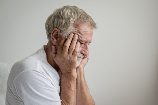 senior man thinking or try to remember alone on bed in white room