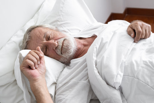 senior man sleeping alone and headache or dreaming nightmare on bed in room
