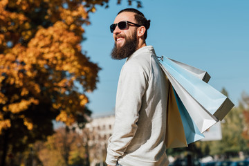 Man fashion style. Bearded hipster guy with shopping bags enjoying autumn sunny day. Blur fall trees and blue sky background.