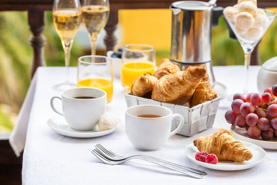 Luxury brunch on the hotel  terrace, coffee maker, cups, croissants, fruits, orange juice and champagne. Good morning scenery background.