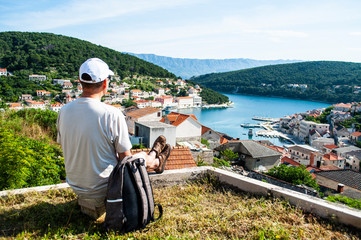 man with  backpack on  mountain, the view of  sea and the European old town, Croatia, the view from the top of the bay, the concept of tourism and travel.