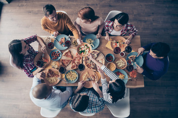 Close up top above high angle view photo festive company social crowd event birthday members share eating process beverage sit table full meals shirts formal-wear sweater pullover loft room indoors