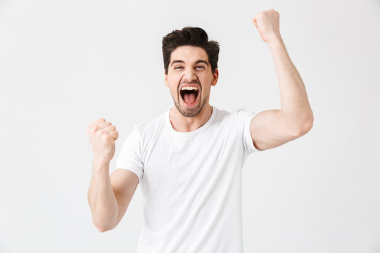 Excited happy young man posing isolated over white wall background.