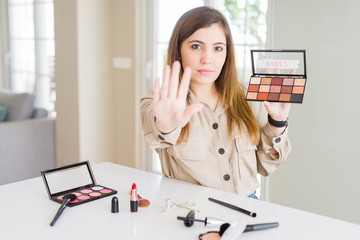 Beautiful young woman using make up cosmetics applying color from palete with open hand doing stop sign with serious and confident expression, defense gesture