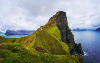 Wall Mural - Small lighthouse located near huge cliffs on island of Kalsoy, Faroe Islands