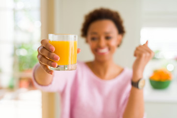 Photo sur Plexiglas Jus, Sirop Young african american woman driking orange juice at home screaming proud and celebrating victory and success very excited, cheering emotion