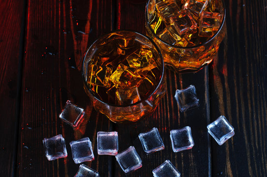 Two glasses of whiskey with ice cubes served on wooden planks.