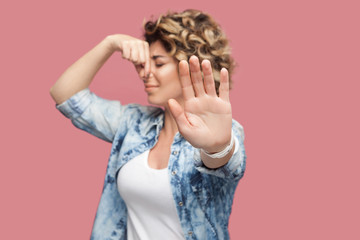 Bad smell blocking. Portrait of dissatisfied young woman with curly hair in casual shirt standing showing stop sign and pinching her nose with confused face. studio shot, isolated on pink background.