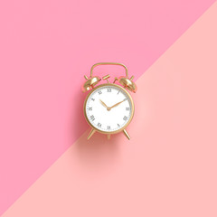 classic gold-colored alarm clock on a two-tone pink background.