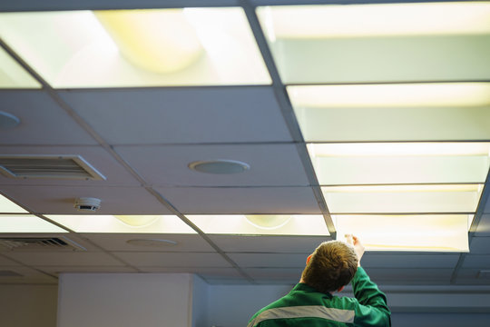 Male electrician in a special uniform changes lamps in lighting devices.