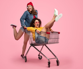 Cheerful young woman pushing shopping cart with friend