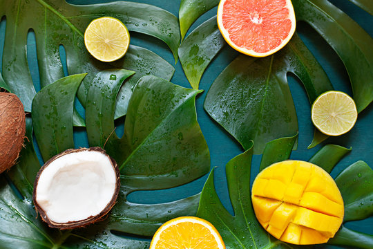 Wet Tropical leaves summer concept frame with exotic fruits on the wooden dark background.