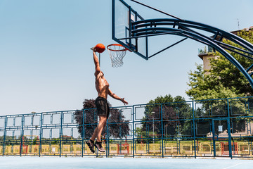 Street basketball player performing slam dunk
