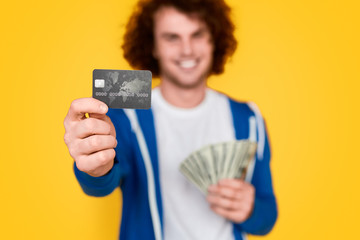 Blurred guy with money demonstrating credit card