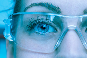 A close up view on the eyes of a pretty young Caucasian lady, working as a technician inside a laboratory, she wears protective goggles, cool blue filter gives futuristic atmosphere. Wall mural
