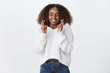Excitement, anticipation surprise concept. Charming smiling happy african-american young woman cross fingers good luck closed eyes smiling gladly make wish dream party went well, white background Fototapete