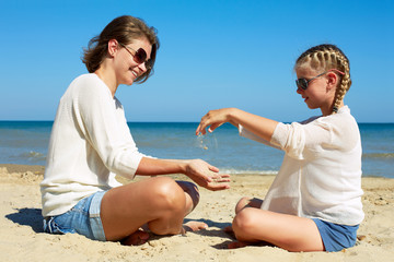 Daughter and her mom playing with sand on the beach.  Time together