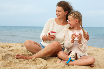 Portrait of a happy parent and child drinking tea on the beach