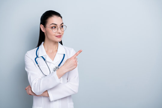 Close up photo beautiful amazing she her lady doctor first working day hospital indicate finger empty space advising use pills wear phonendoscope white science costume specs isolated grey background