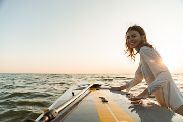 Beautiful smiling young woman using a stand up paddle board