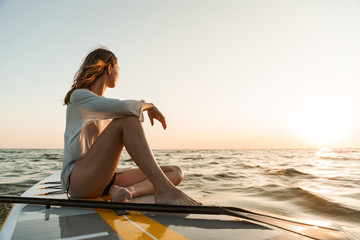 Beautiful young woman sitting on a stand up paddle board