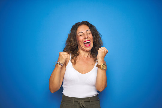 Middle age senior woman with curly hair standing over blue isolated background very happy and excited doing winner gesture with arms raised, smiling and screaming for success. Celebration concept.