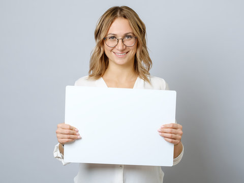 Pretty young woman holding empty blank board isolated