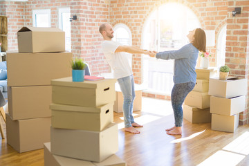 Young couple dancing around cardboard boxes at new home, celebrating smiling very happy new house