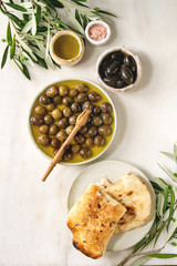 Variety of green and black whole olives in olive oil served in ceramic bowls with fresh baked ciabatta bread, pink salt and young olive wood branches over white marble background. Flat lay, space