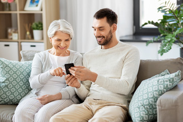 family, generation and people concept - happy smiling senior mother and adult son with smartphone networking at home