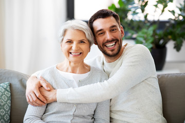 family, generation and people concept - happy smiling senior mother with adult son hugging at home Fotomurales