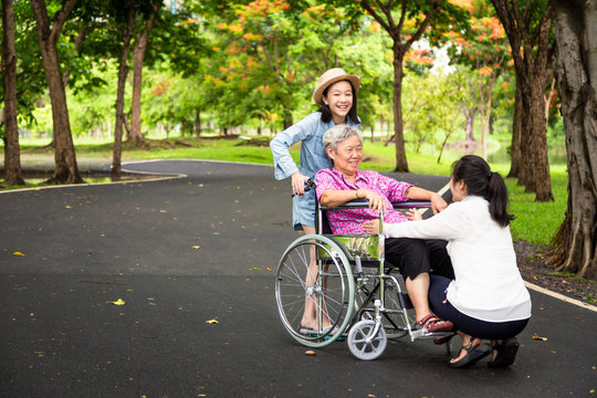 Asian senior woman in wheelchair with little child girl support,enjoy on walking,grandmother with her daughter,granddaughter having fun talk,hug,laughing together in park,elderly care,family concept