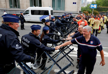 Belgian firefighters shake hands with police officers as they protest for better work conditions in central Brussels
