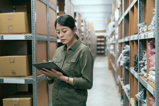 Young woman worker working in warehouse standing and checking supplies on digital tablet. beautiful lady stockroom employee using mobile touchpad doing stocktaking. elegant female staff in storehouse