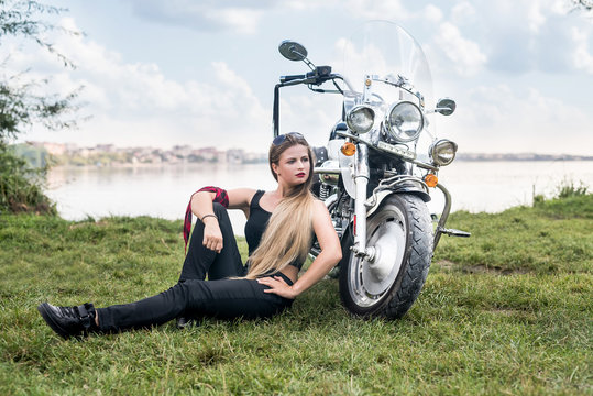 Woman with helmet sitting on the grass near motorcycle
