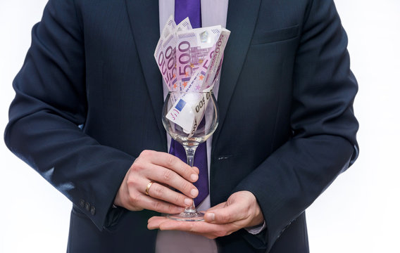Wine glass with euro banknotes in male hands