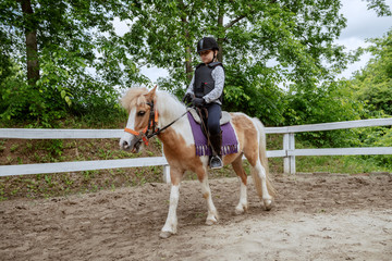 Caucasian girl with helmet and protective vest on riding cute white and brown pony horse. Sunny day...
