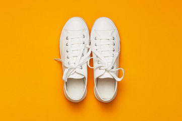 White female fashion sneakers on yellow orange background. Flat lay top view copy space. Women's shoes. Stylish white sneakers. Fashion blog or magazine concept. Minimalistic shoe background, sport Wall mural