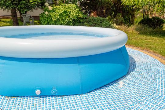 A round, blue, garden pool for children.
