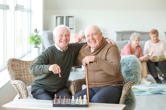 Senior men playing chess in nursing home