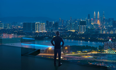 Businessman standing on open roof top balcony watching city night view . Business ambition and vision concept . Fototapete