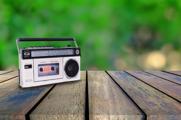 Vintage radio player on wood walk with backround.